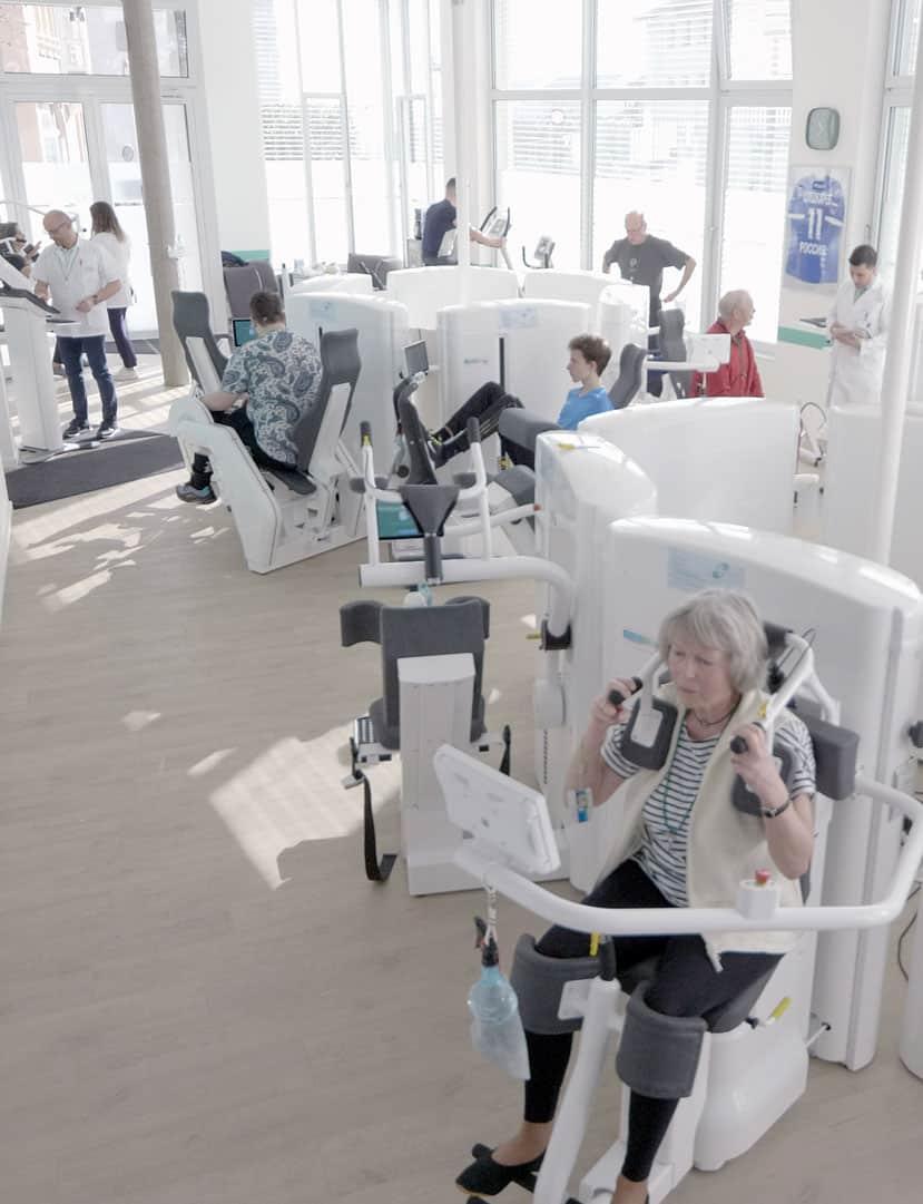 Vue d'ensemble du cabinet de physiothérapie du Dr.E. by Swiss Ortho Clinic, avec les différentes machines. Ambiance éclairée et lumineuse.